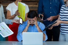 Ejecutivo de operaciones de sexo masculino frustrado que se sienta con el ordenador portátil en el escritorio Fotografía de archivo