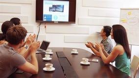 Ejecutivo de operaciones que aplaude durante una videoconferencia