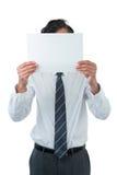 Ejecutivo de operaciones que cubre su cara detrás del papel en blanco Fotos de archivo