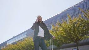 Ejecutivo de publicidad caucásico de sexo masculino con la maleta que habla en el aire libre del smartphone cerca del edificio de metrajes