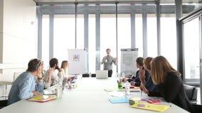 Ejecutivo de publicidad de sexo masculino que da la presentación a los colegas mientras que sostiene la taza metrajes