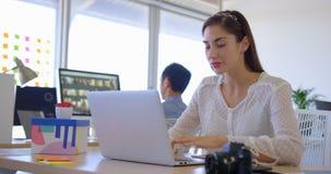 Ejecutivo de sexo femenino caucásico bonito que trabaja en el ordenador portátil en el escritorio 4k metrajes