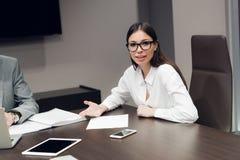 Ejecutivo de sexo femenino joven que sonríe durante el encuentro en la sala de conferencias de la oficina imagen de archivo libre de regalías