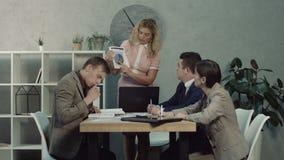 Ejecutivo de sexo femenino que da tareas de funcionamiento a los empleados almacen de metraje de vídeo