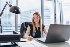 Ejecutivo de sexo femenino que se sienta en su escritorio que toma notas en la escritura de la agenda con la pluma y que usa su o imagen de archivo