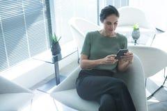 Ejecutivo de sexo femenino que usa el teléfono móvil fotografía de archivo libre de regalías