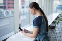 Ejecutivo de sexo femenino que usa el teléfono móvil Foto de archivo libre de regalías
