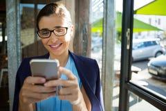 Ejecutivo de sexo femenino que usa el teléfono móvil en café foto de archivo