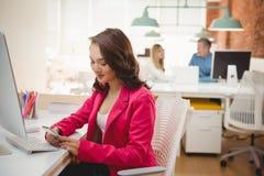 Ejecutivo de sexo femenino que usa el teléfono móvil en el escritorio fotografía de archivo