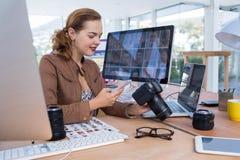 Ejecutivo de sexo femenino que usa el teléfono móvil mientras que mira la cámara digital en oficina Imagen de archivo libre de regalías
