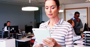 Ejecutivo de sexo femenino que usa la tableta digital