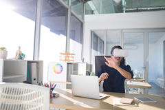 Ejecutivo de sexo femenino que usa las auriculares de la realidad virtual en su escritorio imagen de archivo libre de regalías