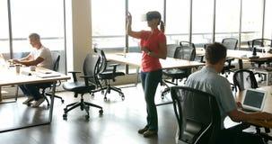 Ejecutivo de sexo femenino que usa las auriculares virtuales de los bienes raices mientras que sus colegas que trabajan en el esc metrajes