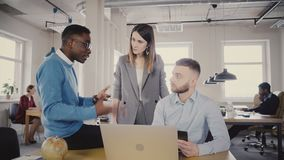 Ejecutivo de sexo femenino serio que ayuda a trabajadores multiétnicos jovenes El encargado de la mujer motiva a empleados preocu almacen de metraje de vídeo