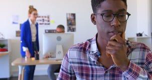 Ejecutivo de sexo masculino afroamericano hermoso que usa el ordenador portátil en la oficina moderna 4k metrajes