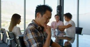 Ejecutivo de sexo masculino asiático joven pensativo que se sienta en la tabla en la sala de conferencias en la oficina 4k almacen de video