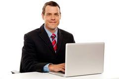 Ejecutivo de sexo masculino en la computadora portátil del funcionamiento del escritorio del trabajo Fotos de archivo libres de regalías