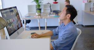 Ejecutivo de sexo masculino joven que trabaja en PC de sobremesa en el escritorio 4k almacen de video