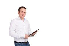 Ejecutivo de sexo masculino joven serio que usa la tableta digital contra el fondo blanco, mirando la cámara Fotografía de archivo libre de regalías