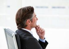 Ejecutivo de sexo masculino pensativo que se sienta en su oficina Imagenes de archivo