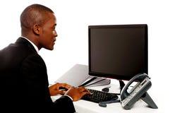 Ejecutivo de sexo masculino que pulsa y que mira la pantalla del lcd Imágenes de archivo libres de regalías