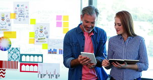 Ejecutivo de sexo masculino que usa la tableta digital mientras que ejecutivo de sexo femenino que observa en el diario