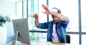 Ejecutivo de sexo masculino que usa las auriculares de la realidad virtual en el escritorio almacen de metraje de vídeo