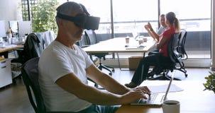 Ejecutivo de sexo masculino que usa las auriculares y el ordenador portátil de la realidad virtual en el escritorio 4k almacen de video