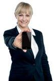 Ejecutivo de ventas que visualiza el teléfono a estrenar de las multimedias Imagen de archivo libre de regalías