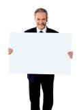 Ejecutivo del puesto de informaciones que muestra la cartelera blanca Foto de archivo libre de regalías