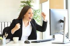 Ejecutivo emocionado que mira un monitor de computadora imagenes de archivo
