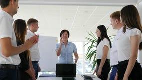 Ejecutivo empresarial alegre que da los pulgares para arriba y palmada con los colegas en oficina moderna metrajes