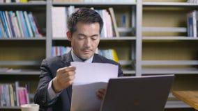 Ejecutivo empresarial asiático que trabaja en oficina metrajes