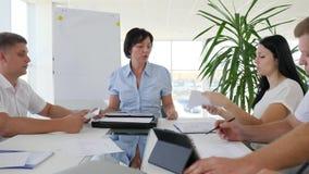 Ejecutivo empresarial con los colegas que discuten nuevas ideas del negocio en la oficina moderna almacen de metraje de vídeo