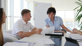 Ejecutivo empresarial que celebra la reunión con el equipo de colaboradores en la tabla en oficina moderna metrajes