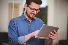 Ejecutivo feliz que usa la tableta digital en la oficina creativa imagen de archivo