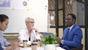 Ejecutivo financiero de sexo femenino y encargado africano que discuten metas del proyecto con el equipo multirracial almacen de metraje de vídeo