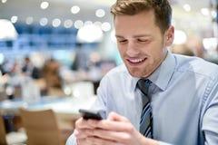 Ejecutivo joven feliz que usa el teléfono elegante Imagen de archivo