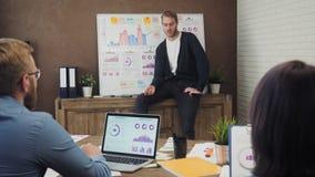Ejecutivo joven que da una presentación en el tablero blanco a los compañeros de trabajo metrajes
