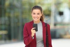 Ejecutivo joven que sostiene un teléfono y que le mira Fotografía de archivo