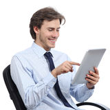 Ejecutivo que se sienta en una silla que hojea una tableta Imagen de archivo