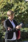 Ejecutivo que trabaja con un teléfono móvil en la calle Foto de archivo
