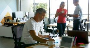Ejecutivo que trabaja en el escritorio mientras que sus colegas que hablan en el fondo 4k metrajes