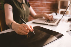 Ejecutivo que trabaja en la aguja mientras que usa el ordenador portátil en oficina imagen de archivo