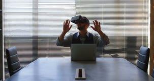 Ejecutivo que usa el ordenador portátil y las auriculares de la realidad virtual en la oficina 4k almacen de metraje de vídeo