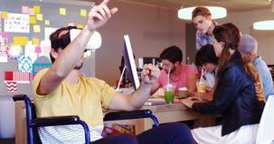 Ejecutivo que usa las auriculares de la realidad virtual en la silla de ruedas