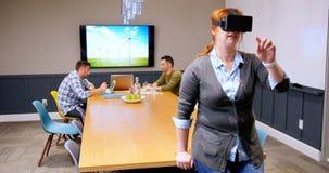 Ejecutivo que usa las auriculares de la realidad virtual mientras que colegas que trabajan en el fondo 4k almacen de metraje de vídeo