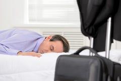 Ejecutivo 'senior' cansado. Hombre de negocios maduro cansado que miente en tan Fotos de archivo libres de regalías