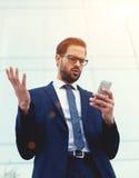 Ejecutivo sorprendido y chocado que mira el teléfono elegante que recibe malas noticias Foto de archivo libre de regalías