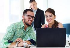 Ejecutivos casuales que trabajan junto en una reunión con el ordenador portátil Imagen de archivo